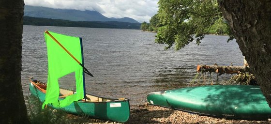 Photo of open canoes with sail on a loch side