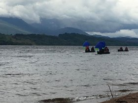 Photo of open canoes sailing on a loch