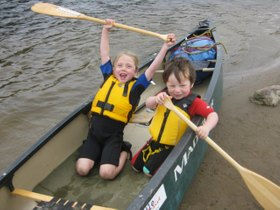 Photo of children in an open canoe