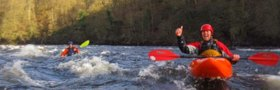 Photo of whitwater kayaker giving thumbs up