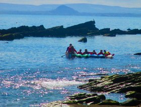 Photo of open canoe on a beach at a sunny loch side